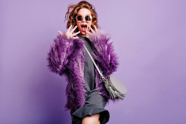Grappig verrast meisje in modieuze kleding schreeuwen op paarse achtergrond