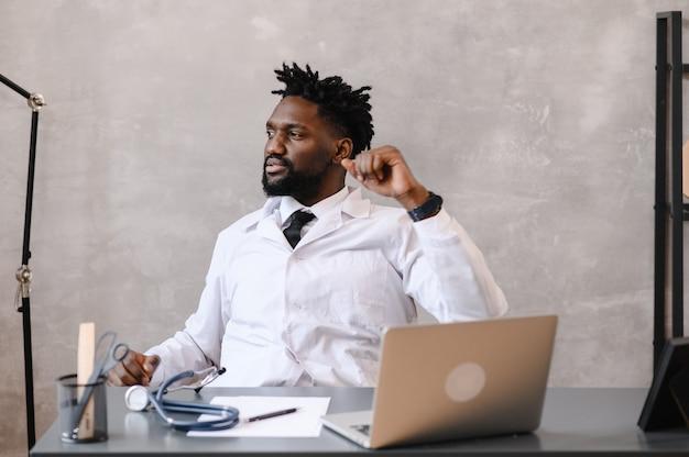 Grappig verveeld op het werk afro-amerikaanse doktersmedewerker die in slaap valt op kantoor, werknemer die op het werk in de buurt van laptop slaapt, voelt zich overwerkt concept