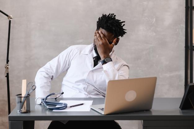 Grappig verveeld op het werk afro-amerikaanse doktersmedewerker die in slaap valt op kantoor