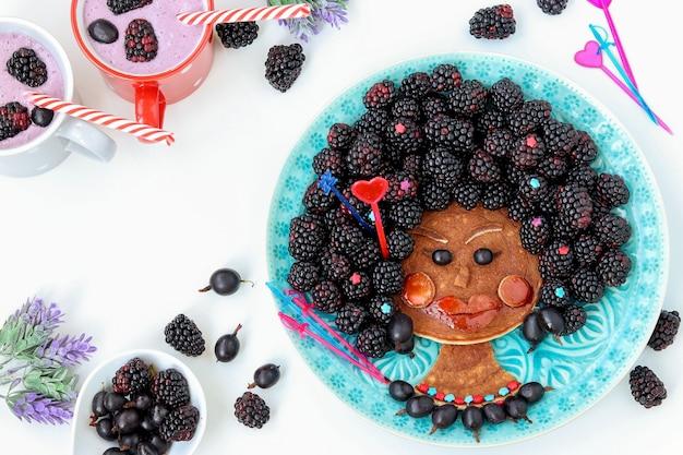Grappig voedselidee voor kinderen eetbaar afrikaans meisje, gezicht van pannenkoek, kruisbes en braambes