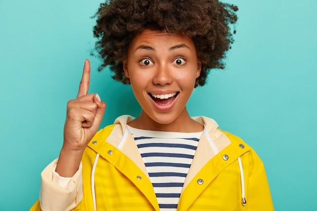 Grappig vrolijk afro-meisje met donker krullend haar, wijsvinger omhoog wijst, iets hierboven demonstreert, heeft wijd geopende ogen