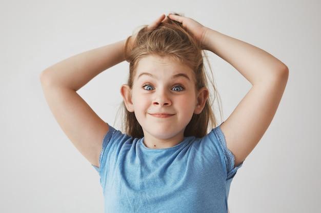 Grappig vrolijk blondemeisje die met blauwe ogen haar met handen, met opgeheven wenkbrauwen en dwaze gezichtsuitdrukking houden