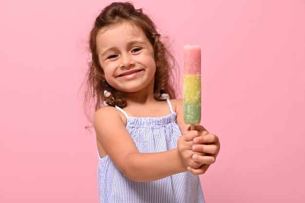 Grappig vrolijk meisje glimlacht en toont aan de camera een heerlijk zoet bevroren sap, ijslolly, ijs in haar handen. zomerconcept voor reclame, roze achtergrond, kopieerruimte voor promotie