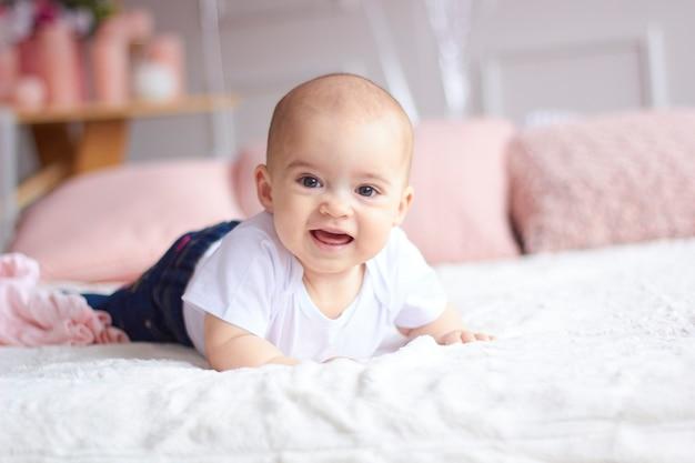 Grappig weinig babymeisje in roze helder modern binnenland