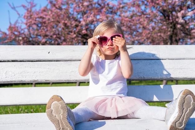 Grappig weinig zitting van het babymeisje op witte bank in stadspark in roze glazen bij de zomer
