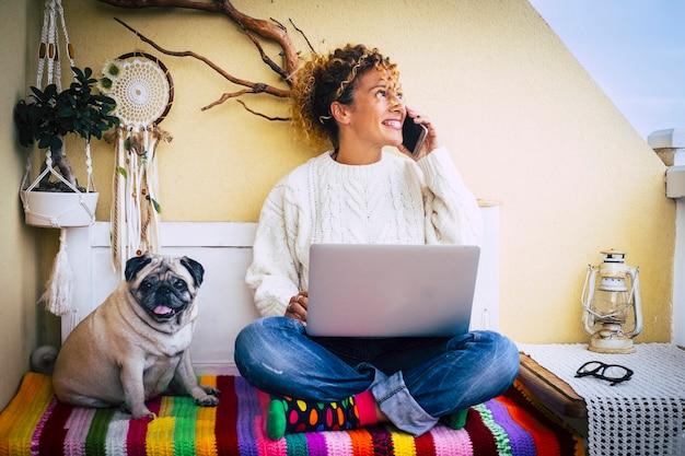 Grappig werk en technologie concept foto met volwassen vrolijke blanke jonge mooie vrouw die belt aan de telefoon en laptopcomputer gebruikt en schattige mooie hond pug beste vriend in de buurt van haar