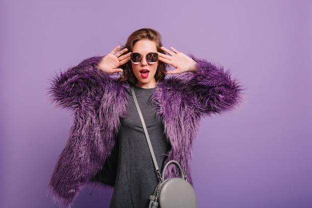 Grappig wit meisje draagt een elegante zonnebril die gezichten op paarse achtergrond maakt