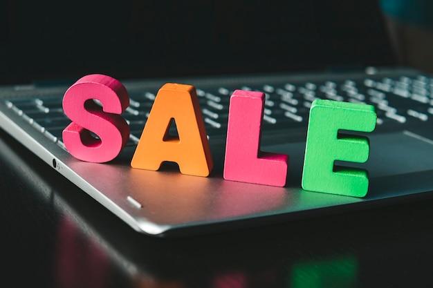 Grappig woord sale ingesteld op de onderkant van het notitieboekje. kleurrijk teken verkoop op zwarte oppervlakte bij het zwarte schermachtergrond. online winkelconcept. internet marketing. e-commerce. houten letters promoten e-shopping.