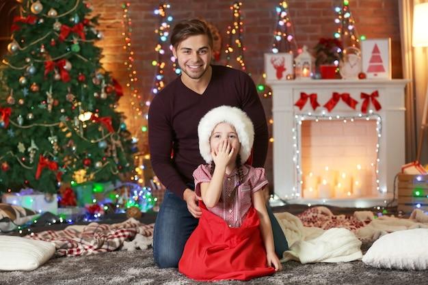 Grappig zusje in santa zak verrassend haar oudere broer op kerstmis