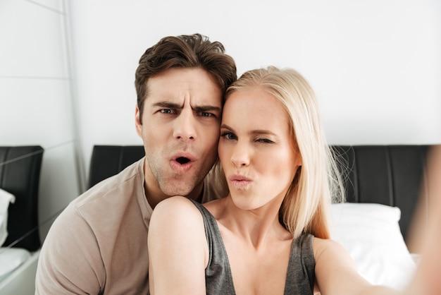 Grappige aantrekkelijke liefhebbers maken selfie en grimassen in de ochtend