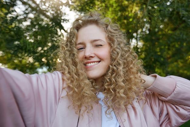 Grappige aantrekkelijke mooie blonde vrouw met krullend haar, selfie maken op eigen telefoon voor sociale netwerken