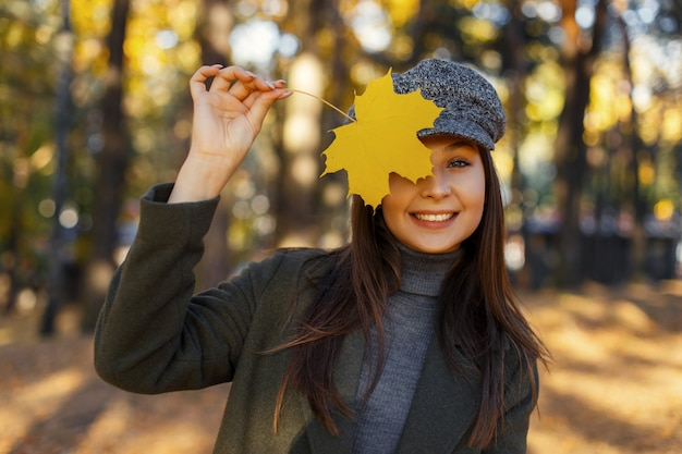Grappige aantrekkelijke mooie jonge gelukkig vrouw met een glimlach in een vintage hoed en jas heeft betrekking op haar gezicht met een gele herfstblad en geniet van een zonnige dag