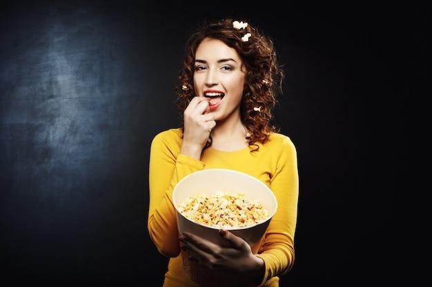 Grappige aantrekkelijke vrouw die smakelijke zoute zoete popcorn eet bij bioskoop