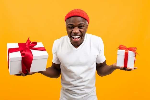 Grappige afrikaanse man met een glimlach in een wit t-shirt houdt twee dozen een geschenk met een rood lint voor valentijnsdag op een gele studio achtergrond