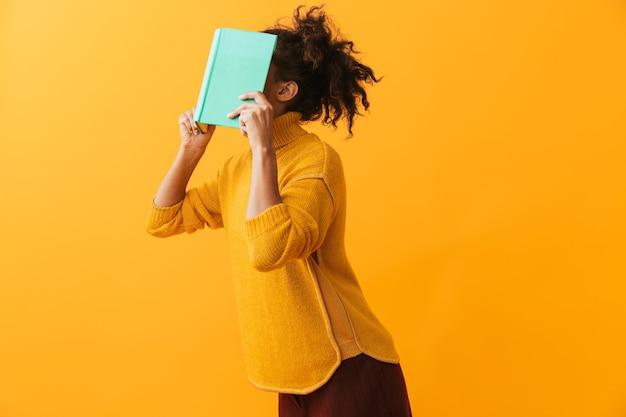 Grappige afrikaanse vrouw die sweater draagt die een boek op haar geïsoleerd gezicht houdt