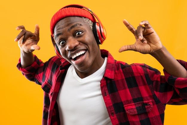 Grappige afrikaanse zwarte man stijlvol gekleed met een grimas op zijn gezicht luistert naar muziek met een koptelefoon op een gele studio achtergrond