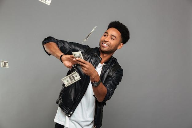 Grappige afro amerikaanse rijke man die dollarsbankbiljetten verspreiden