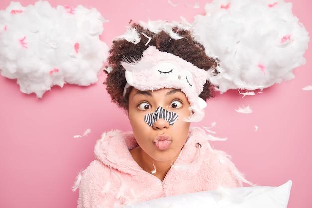 Grappige afro-amerikaanse vrouw maakt grimas heeft applicator masker op neus kruist ogen ondergaat schoonheidsprocedures voor een gezonde zachte huid gekleed in nachtkleding poses met kussen met veren eromheen