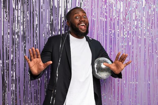Grappige afro-man in stijlvol pak, houdt glanzende discobal vast, danst en zingt op muziek, viert een afscheidsfeestje met vrienden, heft palmen op, is in een hoge geest, geïsoleerd over versierde paarse muur
