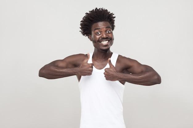 Grappige afro man met snor, camera kijken, glimlachen, duimen omhoog. studio opname. grijze achtergrond