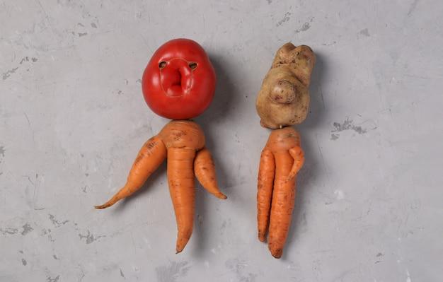 Grappige agli groenten tomaat, aardappel en wortelen op grijze achtergrond, lelijk voedselconcept, horizontaal formaat, uitzicht van bovenaf