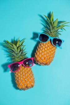 Grappige ananas in een zonnebril op blauwe achtergrond