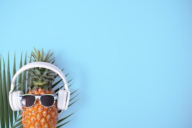 Grappige ananas met witte hoofdtelefoon, concept van het luisteren muziek, geïsoleerd op blauwe achtergrond met tropische palmbladeren