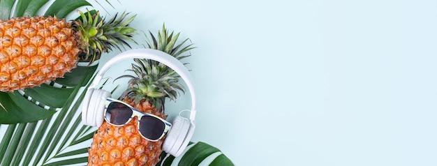 Grappige ananas met witte hoofdtelefoon, concept van luisteren muziek, geïsoleerd op een gekleurde achtergrond met tropische palmbladeren, bovenaanzicht, plat ontwerp.