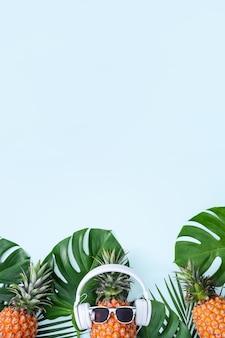 Grappige ananas met witte hoofdtelefoon, concept van muziek luisteren, geïsoleerd op blauwe achtergrond met tropische palmbladeren, bovenaanzicht, plat ontwerp.