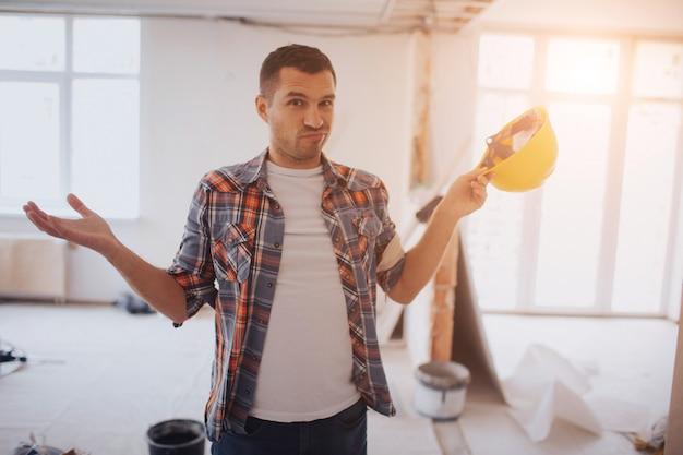 Grappige arbeider met bouwhelm staat op de bouwplaats en weet niet wat te doen.