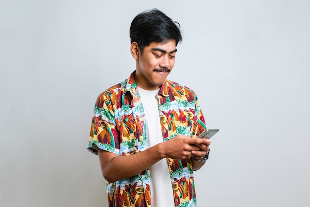 Grappige aziatische guy spelen op tablet smart phone tegen witte achtergrond
