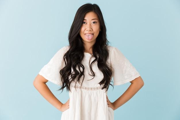 Grappige aziatische mooie vrouw die over blauwe muur wordt geïsoleerd die tong toont