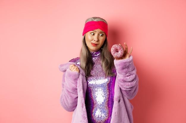 Grappige aziatische senior vrouw in glinsterende discojurk en namaakbontjas die verleidt naar heerlijke donut, die zoet wil eten, over roze achtergrond staat