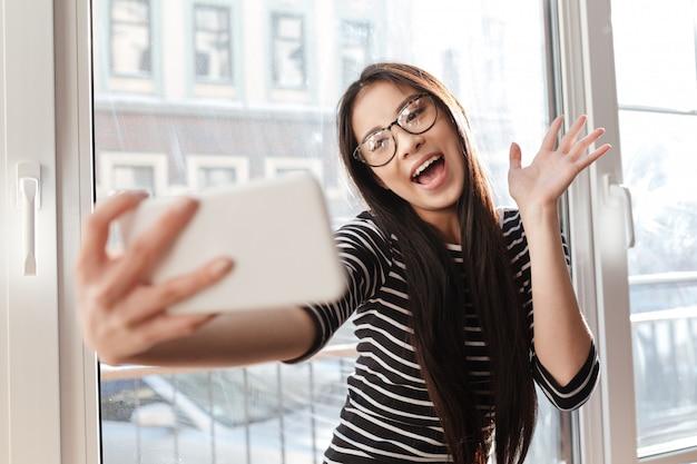 Grappige aziatische vrouw die selfie op vensterbank maken