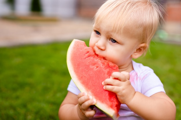 Grappige baby die watermeloen in openlucht in het park eet. baby, baby, gezond eten