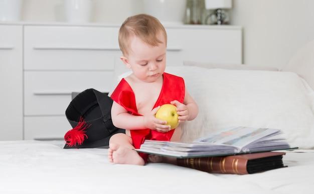 Grappige baby in afstudeerpet en lint die appel vasthoudt en een groot boek leest