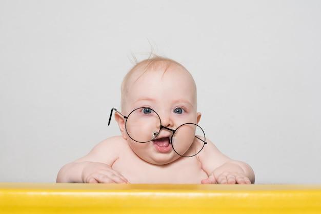 Grappige baby in grote ronde glazen aan de tafel