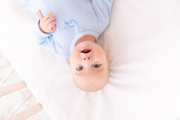Grappige baby kijkt naar de camera liggend in de wieg, portret