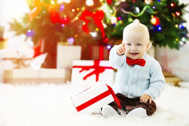 Grappige baby met geschenkdoos en kerstboom