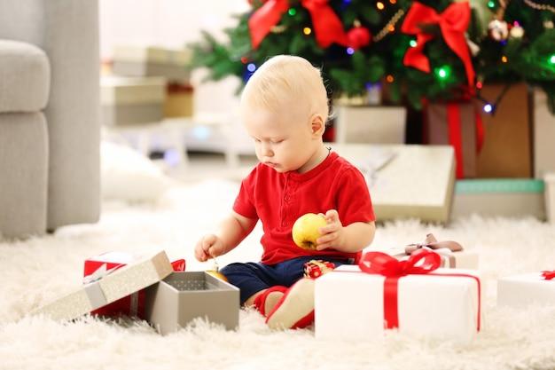 Grappige baby met geschenkdozen en kerstboom