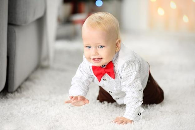 Grappige baby op pluizig tapijt op het oppervlak van de open haard