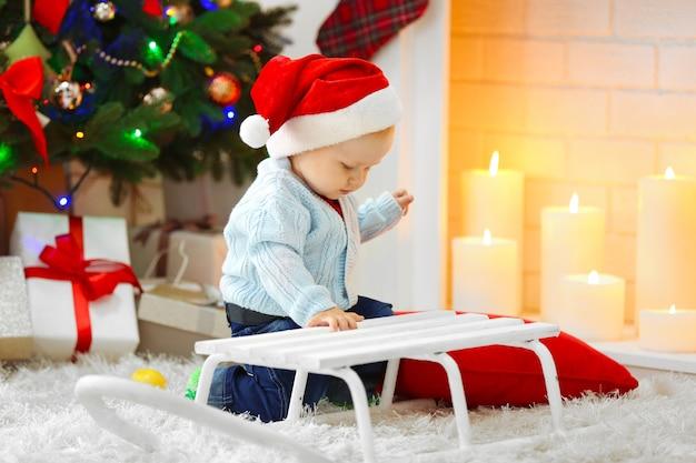 Grappige baby zitten in de buurt van slee en kerstboom en open haard op achtergrond