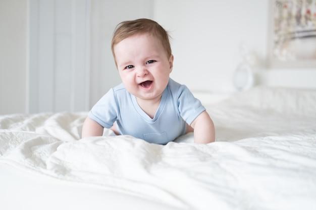 Grappige babyjongen 6 maanden oud in blu romper glimlachend en liggend op bed thuis.