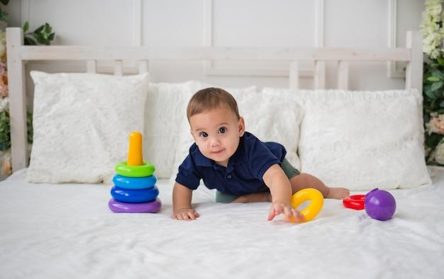 Grappige babyjongen en speelt met een piramidestuk speelgoed op een wit bed