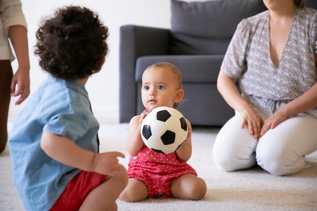 Grappige babymeisje bedrijf voetbal, zittend op een tapijt en spelen met broer in de kamer. bijgesneden moeders die plezier hebben met kinderen. achteraanzicht van krullende jongen. familie binnenshuis, weekend en jeugdconcept
