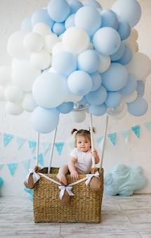 Grappige babymeisje, zittend in een rieten mand met ballonnen