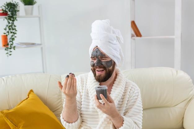 Grappige bebaarde man die plezier heeft met een cosmetisch masker op zijn gezicht gemaakt van zwarte klei mannen huidverzorging