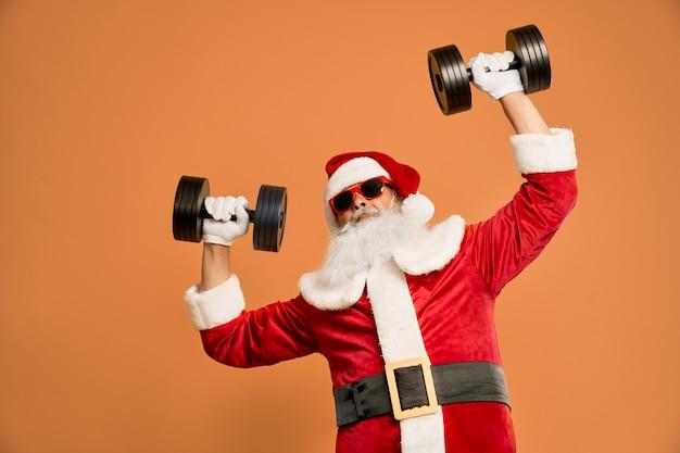 Grappige bebaarde man in santa kostuum met halters boven het hoofd