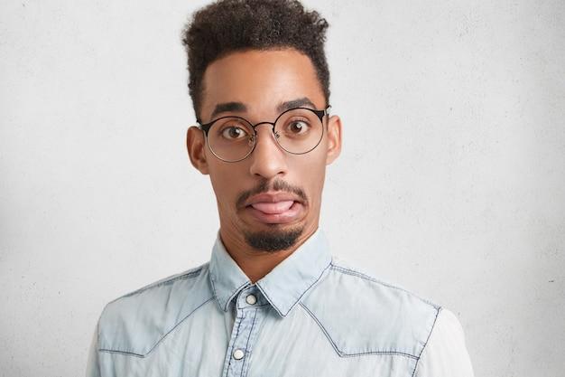 Grappige bebaarde man met aantrekkelijk uiterlijk maakt gek, toont tong, heeft een verrassende uitdrukking