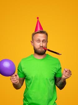Grappige bebaarde man met ballon partij hoorn blazen en camera kijken terwijl het vieren van verjaardag geïsoleerd op geel